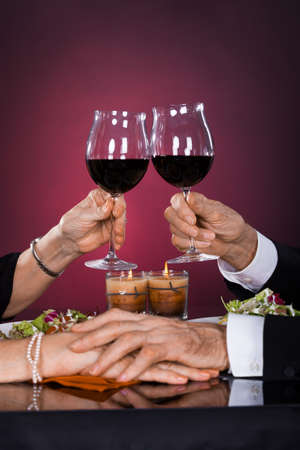 wine and dine: Close-up Of Senior Couple Hand Toasting Wineglass At Dinner Stock Photo