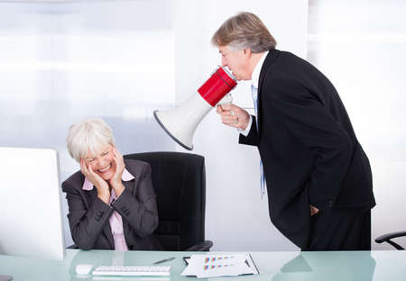 Mature Businessman Yelling At His Coworker With Megaphone At Work photo
