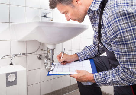 Close-up Of Plumber Standing In Front Of Washbasin Writing On Clipboard Stock Photo