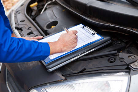 bonnet: Close-up Of A Mature Mechanic Maintaining Car Records Stock Photo