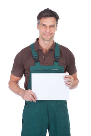 Portrait Of Mature Male Gardener Holding Blank Placard Over White Background photo