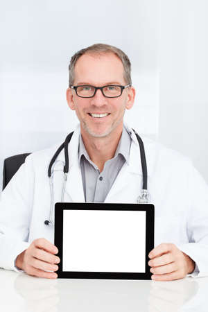 Happy Mature Doctor Showing Blank Digital Tablet In Clinic photo