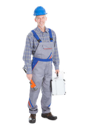 Happy Young Worker Holding Toolbox And Wrench On White Background photo