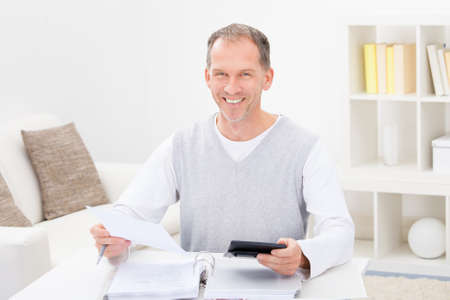 Happy Mature Man Sitting On Couch At Home Holding Calculator And Bills photo