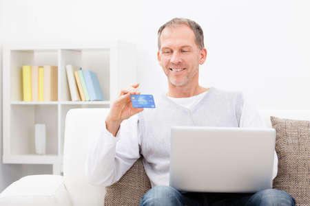 Mature Man Sitting On Couch Showing Credit Card And Laptop photo