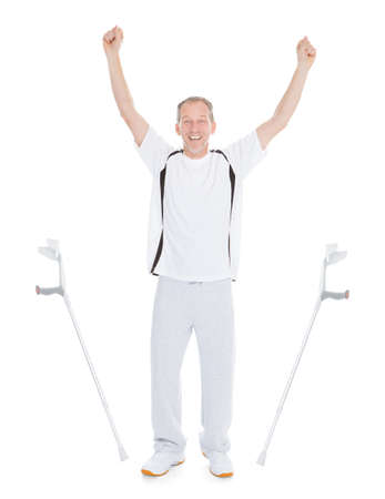 Excited Mature Man Leaving Crutches Over White Background photo