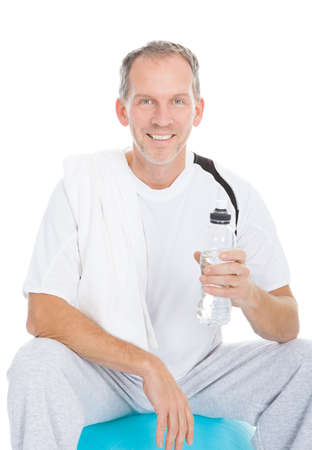 Man Sitting On Pilates Ball Holding Water Bottle After Exercise photo