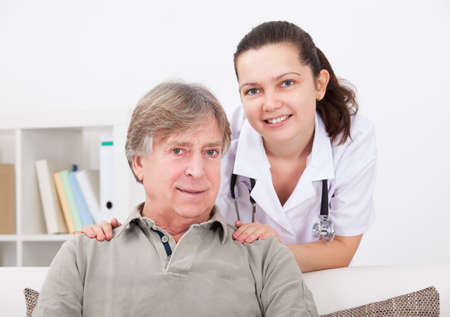 Portrait Of Happy Female Doctor With Mature Patient photo