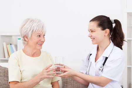 Happy Doctor Offering Glass Of Water To Mature Patient photo
