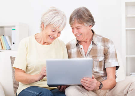 Portrait Of Happy Senior Couple Sitting On Couch Using Laptop photo