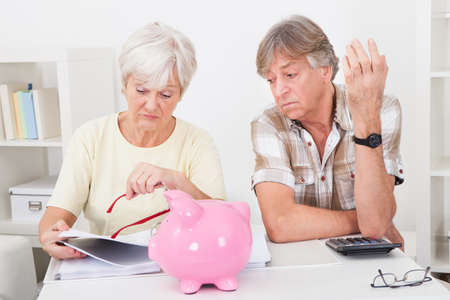 Portrait Of Upset Senior Couple Calculating Finance At Home photo