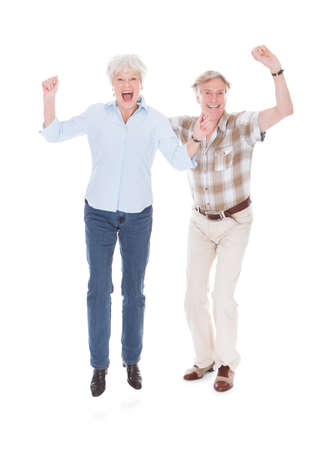 Excited Senior Couple Raising Hand Over White Background photo
