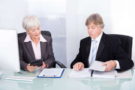 Mature Businessman And Businesswoman Working With Documents And Calculator photo