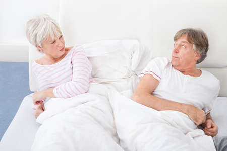 Angry Senior Couple Lying On Bed Looking At Each Other