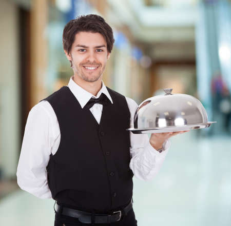 Portrait Of Young Male Waiter Holding Silver Tray photo