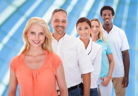 file d attente: Groupe de personnes multi-raciales debout dans une rangée Au Bureau