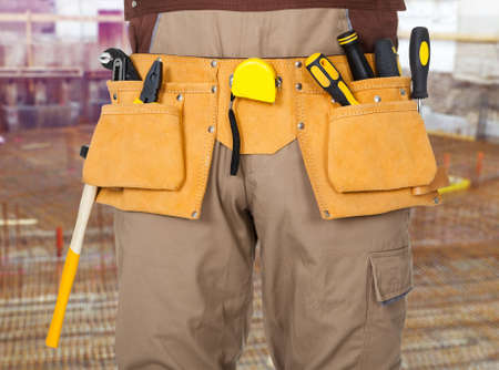 tools belt: Close-up Of Repairman Standing With Tools Belt