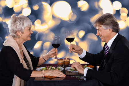 Happy Senior Couple Dining Together With Wine In A Restaurant Stock Photo