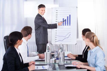 recursos financieros: Hombre de negocios maduro explicar Gráfico a sus colegas que se sientan en la oficina