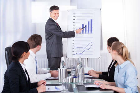 advisor: Mature Businessman Explaining Graph To His Colleagues Sitting In Office