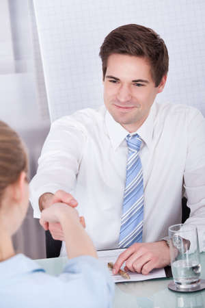 Portrait Of Businessman And Businesswoman Shaking Hands In Office photo