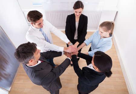 compromiso: Retrato de exitosos empresarios poner sus manos encima de uno al otro