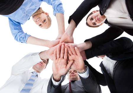 Low Angle View Of Businesspeople Stacking Hands Together Over White Background photo
