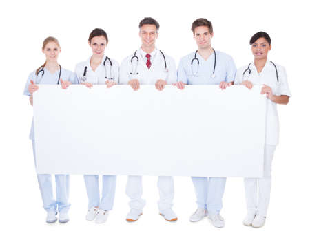 Happy Group Of Doctors Holding Blank Billboard Over White Background photo