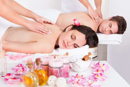 massage therapy: Young Couple In Spa Salon Getting Back Massage Stock Photo
