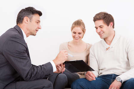 financial insurance: Male Consultant Showing Clipboard To Happy Young Couple Stock Photo