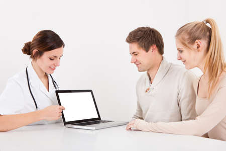 Happy Couple Looking At Blank Screen Laptop With Female Doctor photo