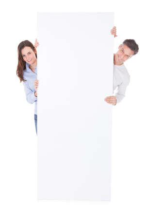 Man And Woman Holding Blank Billboard Over White Background photo
