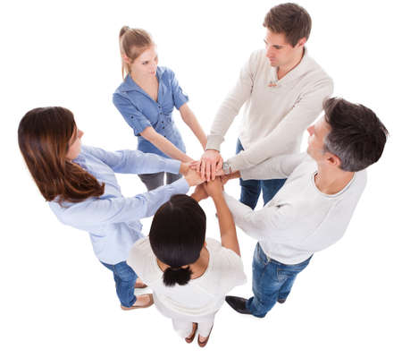 african solidarity: Group Of People Stacking Hand Together Over White Background Stock Photo