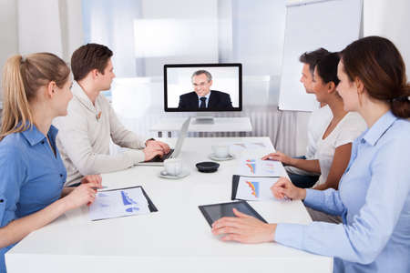 info business: Businesspeople Sitting In Conference Room Looking At Monitor Stock Photo