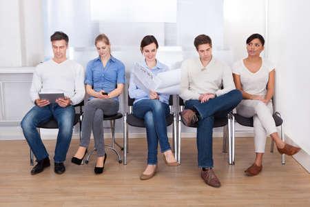 full: Grupo de personas que se sientan en silla en una sala de espera