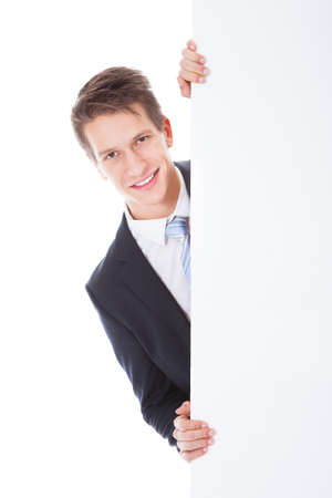 Portrait Of Young Businessman Holding Blank Placard Over White Background photo