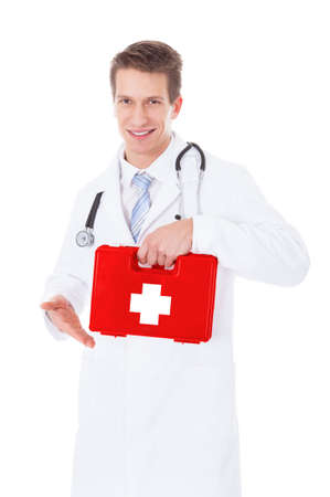 Portrait Of Young Male Doctor Holding Red First Aid Box photo
