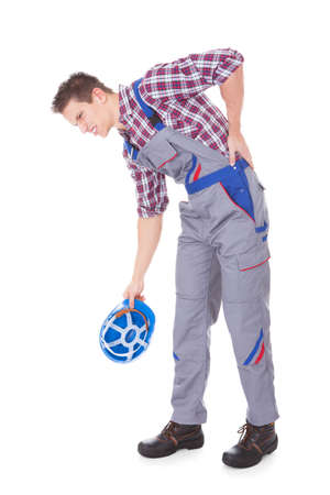 Young Male Worker Suffering From Back Pain Over White Background photo