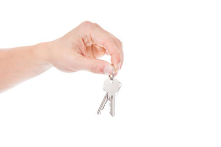 Close-up Of Person Holding Keys Over White Background photo