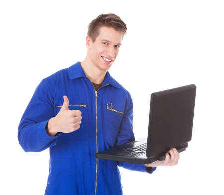 Young Male Technician Using Laptop Over White Background photo