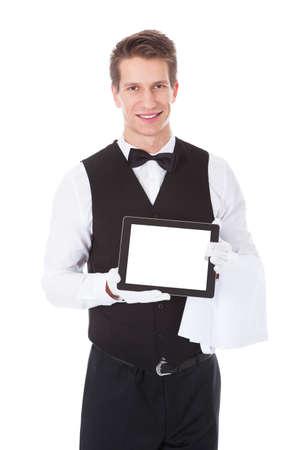 Junge männliche Kellner, der Tablet PC über weißen Hintergrund