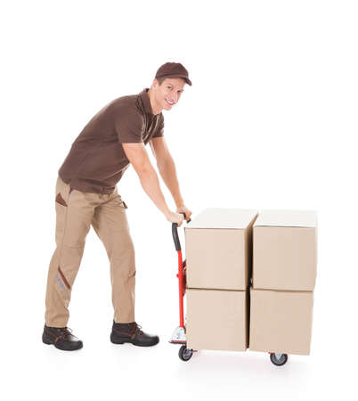 delivery service: Happy Delivery Man Standing With Boxes On Hand truck Over White Background