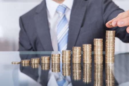 incremento: El hombre de negocios puso la moneda a alto pila de monedas Foto de archivo