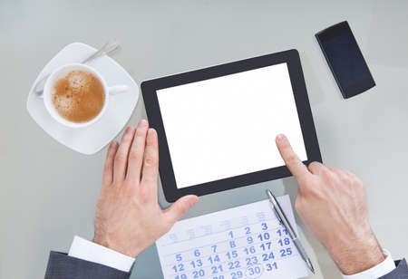 Businessperson Hand Holding Blank Digital Tablet With Coffee Cup And Calendar On Table photo