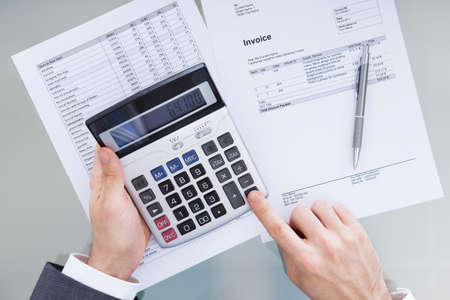 Close-up Of Businessperson Analyzing Financial Data  photo