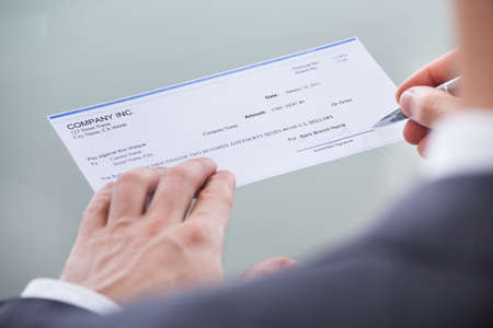 Close-up Of Businessperson Signing Money Cheque With Pen photo