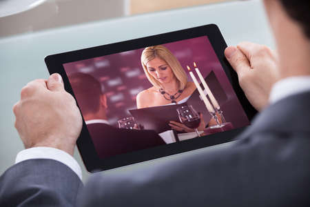 Close-up Of Businessman Watching Video On Digital Tablet photo