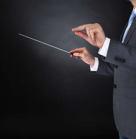 conduct: Close-up Of Orchestra Conductor Hands Holding Baton Over Black Background