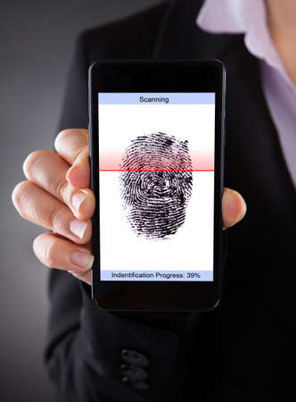 Close-up Of Businessperson With Cellphone Scanning A Fingerprint  photo