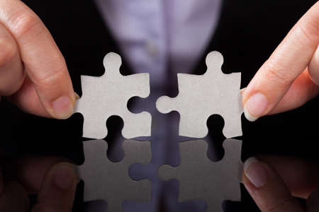 Close-up Of Businessperson Holding Two Puzzle In Hand photo
